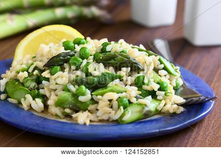 Green asparagus pea parsley and brown rice risotto served on plate photographed on dark wood with natural light (Selective Focus Focus on the asparagus heads on the top of the dish)