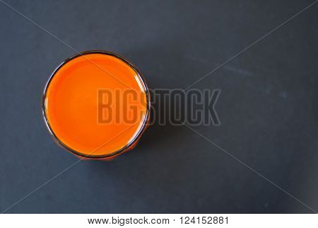Homemade fresh-squeezed carrot juice in glass on black wooden background. View from top.