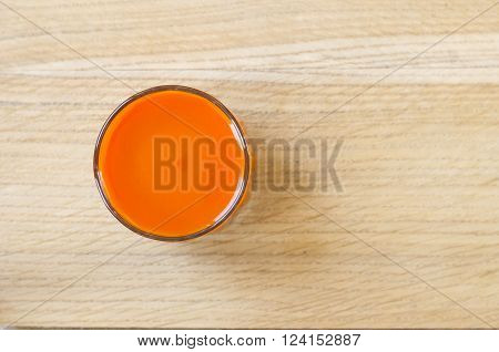 Homemade fresh-squeezed carrot juice in glass on rustic wooden background. View from top.