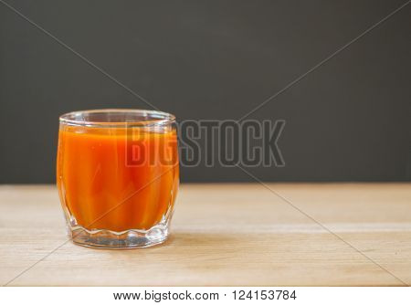Homemade fresh-squeezed carrot juice in glass on black wooden background.