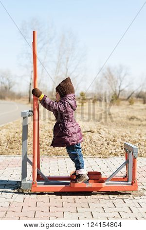 Little girl standing on a trainer outdoor in a spring time