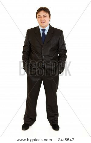 Smiling businessman keeping his hands in trousers pockets isolated on white