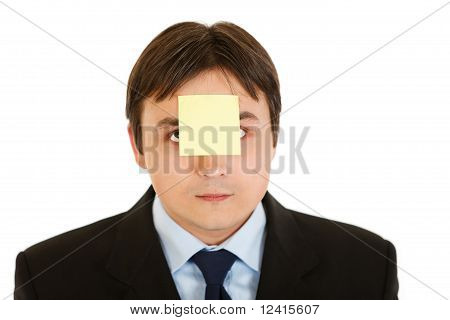 Young businessman with blank adhesive note over his mouth isolated on white