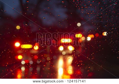 Flashing red and yellow lights of emergency vehicles and firetrucks seen on a rainy night through a wet car windshield