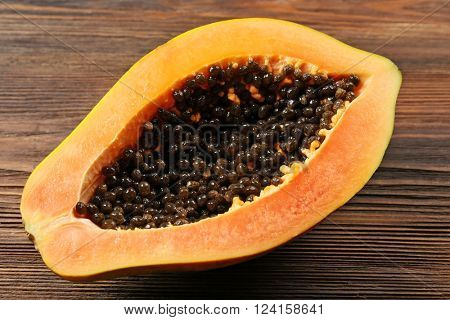Halved papaya on wooden background