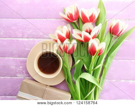 Bouquet of variegated tulips with cup of coffee and gift box on wooden background