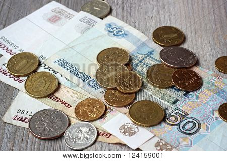 Russian paper money and metal on wooden table top view. Rubles and kopecks.