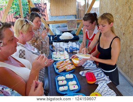 Lazarevskoe, Russia - august 08, 2012, Tourists tasting Adygei cheese on the product presentation, Lazarevskoe