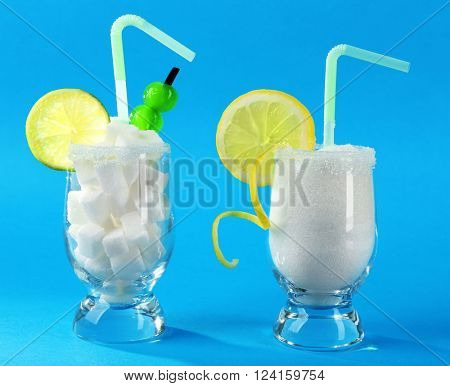 Glasses with granulated, lump sugar, cocktail straws, cherries and citrus slices on blue background