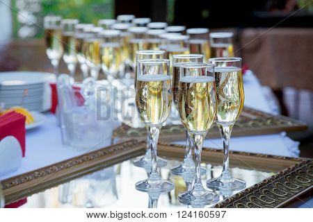 The Wedding Banquet. Banquet in the restaurant. Glasses of champagne in several rows on a mirror tray on the table with a white tablecloth.