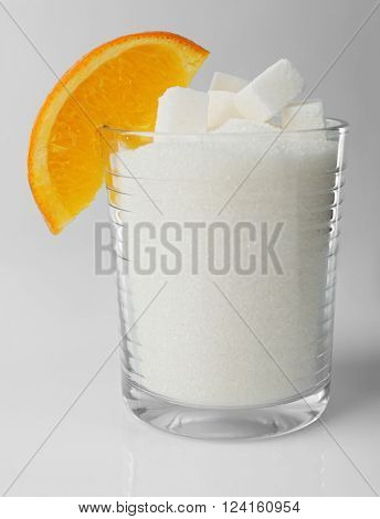 Old fashioned glass with lump, granulated sugar and slice of orange on grey background