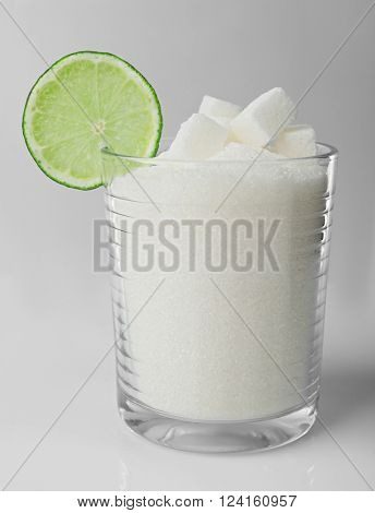 Old fashioned glass with lump, granulated sugar and slice of lime on grey background