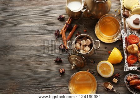 Cup of brewed tea with lemon, eastern sweets and spices on wooden table