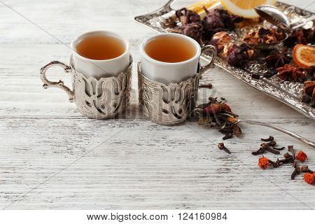 Two cups of brewed tea with spices on light wooden table