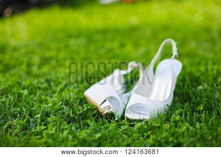white shoes on green grass bridal white shoes on green lawn. Wedding shoes.