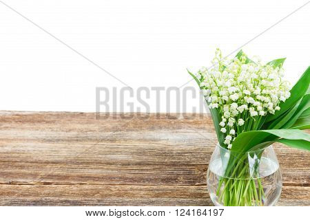 Lilly of valley flowers in glass vase on wooden table border isolated on white background