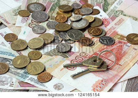 The keys of Russian paper money and metal on wooden table top view. Rubles and kopecks.