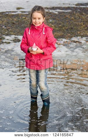 Happy little girl in rain boots playing with ships in the spring creek standing in water. Kids play outdoors