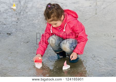 Happy cute little girl in rain boots playing with handmade colorful ships in the spring water puddle. Kids play outdoors