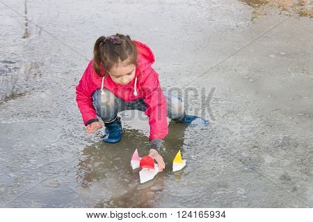 Happy cute little girl in rain boots playing with colorful ships in the spring water puddle. Kids play outdoors