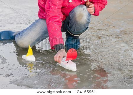 Little girl in rain boots playing with ships in the spring water puddle. Kids play outdoors