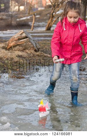 Cute little girl in rain boots playing with handmade ships in the spring creek standing in water. Kids play outdoors