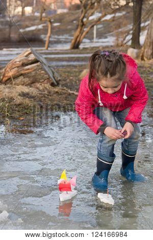 Cute little girl in rain boots playing with ships in the spring creek standing in water. Kids play outdoors
