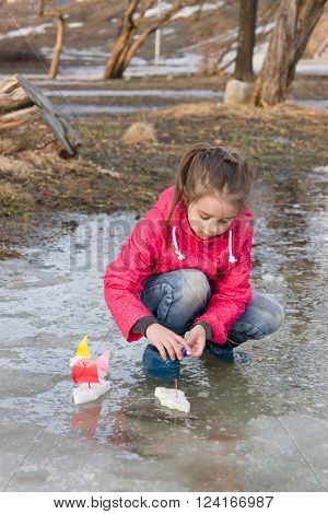 Cute little girl in rain boots playing with handmade ships in the spring water puddle. Kids play outdoors