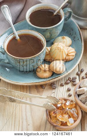 Two blue cups of black coffee biscuits and sugar pieces surrounded by linen cloth and sugar-tongs on old wooden table ** Note: Shallow depth of field