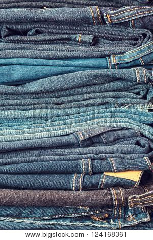 Stacked fashion different blue jeans closeup in store