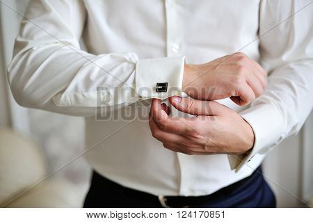 man wear a white shirt and cufflinks