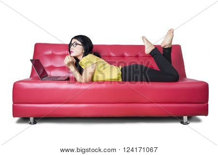 Picture of beautiful female model lying on the sofa while daydreaming with a laptop computer isolated on white background