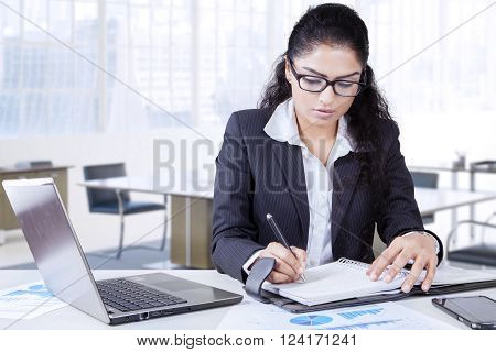 Indian young businesswoman working in the office with laptop computer and writes a journal on the notebook