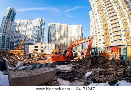 SAMARA RUSSIA - MARCH 29 2016: Construction machinery stands near a apartment buildings under construction