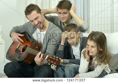 young  man playing the guitar for his family