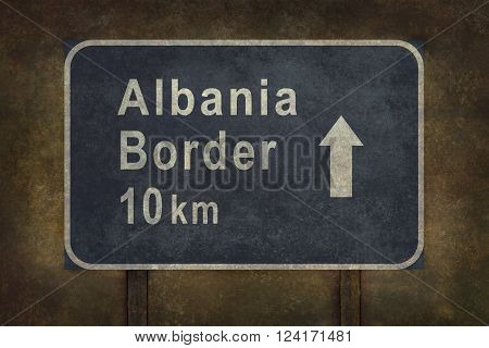 Albania border 10 km directional roadside sign illustration with distressed ominous background