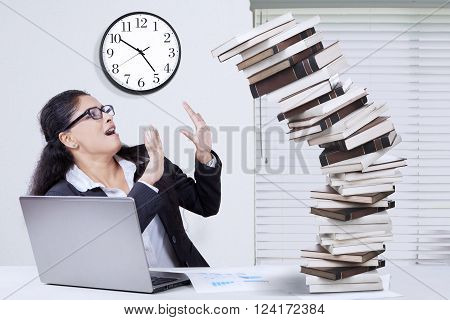 Indian young businesswoman working overtime and tries to hold a pile of falling book