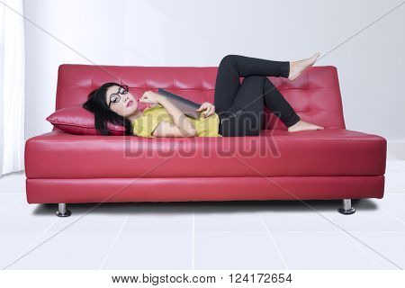 Beautiful young Asian woman smiling at the camera while lying on the sofa and holding a novel