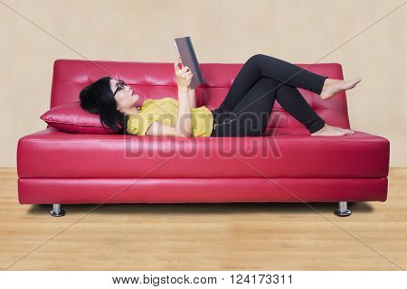 Beautiful young woman reading a storybook while lying on the couch at home