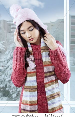 Portrait of beautiful girl wearing a knitted sweater and hat getting headache at home in winter day