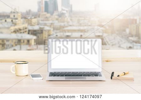 Desktop with blank white laptop iron mug and other items on blurry sunlit city background. Mock up