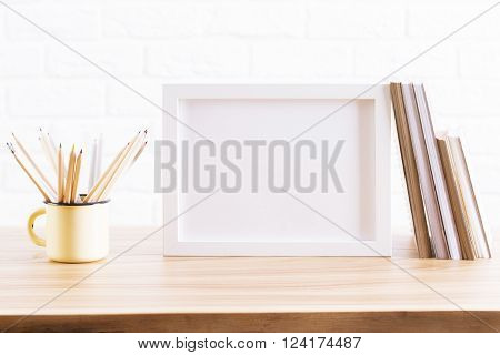 Wooden desktop with blank picture frame pencils in iron mug and book. Mock up