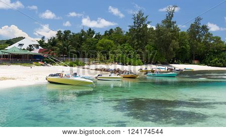 La Digue - 10 November 2014: The boats of fishermen stand on the sandy beach and people are going to go fishing on a sunny day November 10 2014 the island of La Digue Seychelles