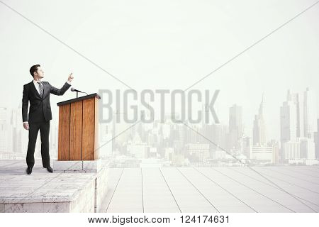 Caucasian businessman in black suit speaking from tribune on foggy city background