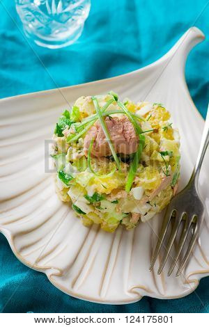 Salad with  potato and cod liver on the plate