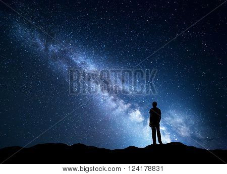 Landscape with blue Milky Way. Night sky with stars and silhouette of a happy man on the mountain. Beautiful Universe. Space background