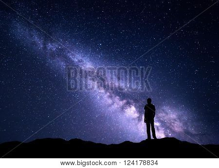 Landscape with purple Milky Way. Night sky with stars and silhouette of a happy man on the mountain. Beautiful Universe. Space background