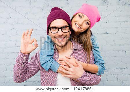 Cute Girl Huging Her Boyfriend And Boy In Glasses Gesturing