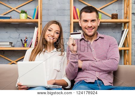 Man And Woman Making Internet Shopping With Laptop And Bank Card