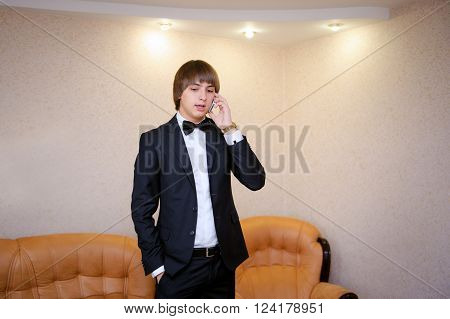 groom in a black suit talking on the phone.